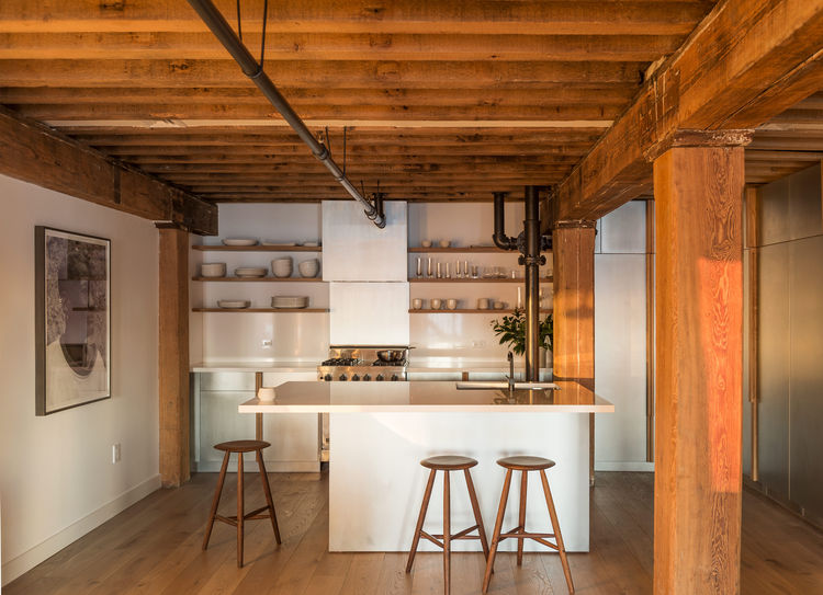 Counter stools from Sawkille, fir beams, and white oak floors in Manhattan apartment