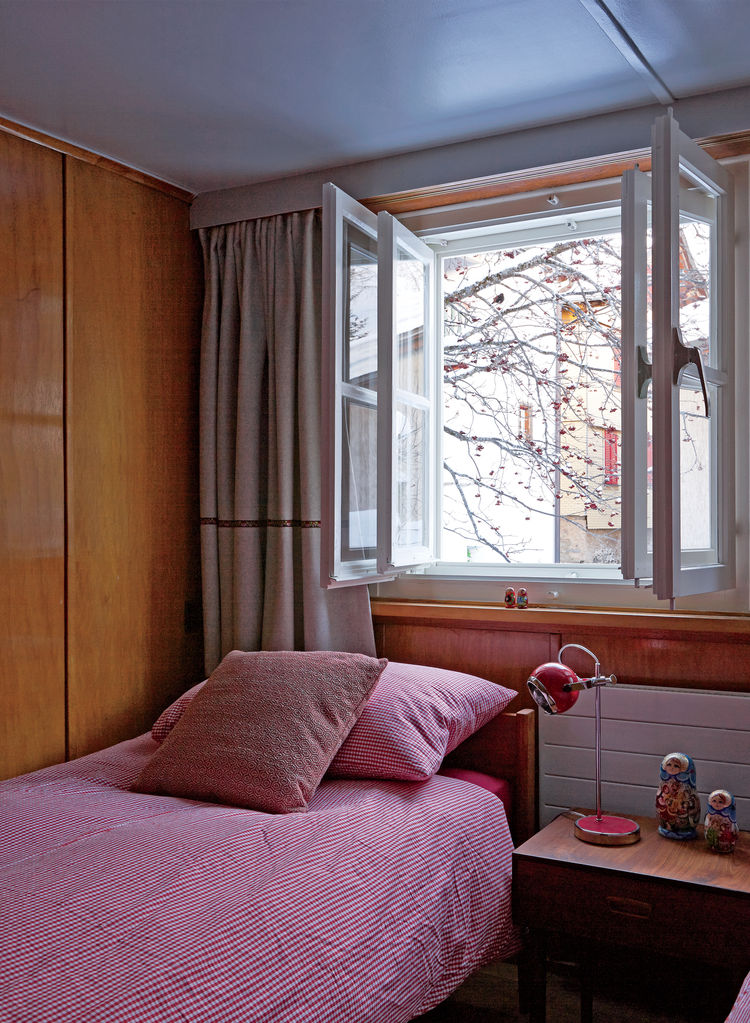 Swiss family getaway small space renovation with bedroom with rosewood bed and side tables and double windows