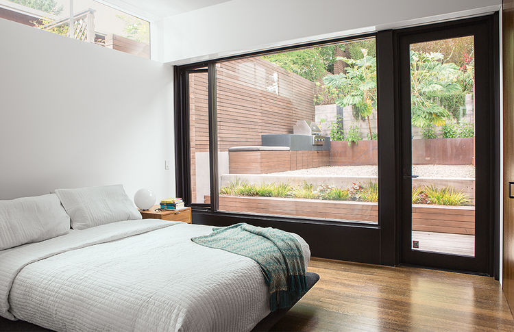 San Francisco master bedroom with a glass wall and a clerestory window