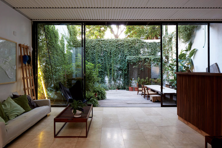 The living room features a corrugated sheet metal ceiling and plants.