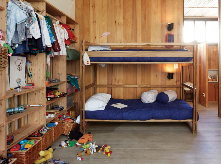The children's bedroom features bunk beds and a lot of toys.