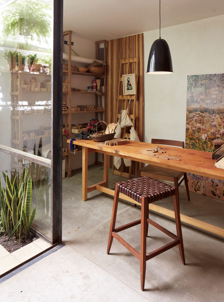 A leather stool and wood table complete a modern studio in Argentina.