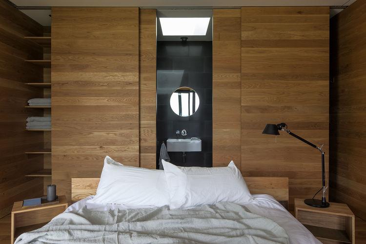Bedroom with oak walls in New Zealand island escape.
