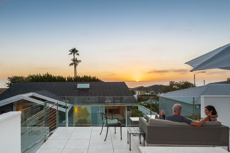 Rooftop patio with Crate & Barrel couch and Hausers umbrella in San Diego renovation by Magnus Architects.