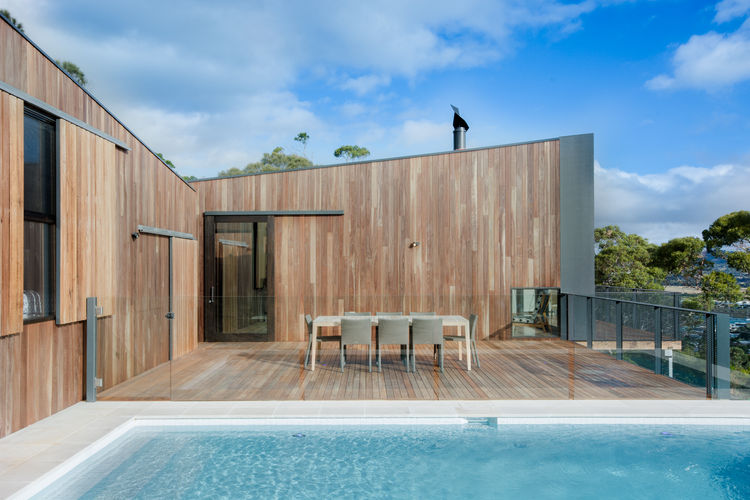 White tile and tan travertine pool pavers of pool at an Australian beach home by OLA Studio