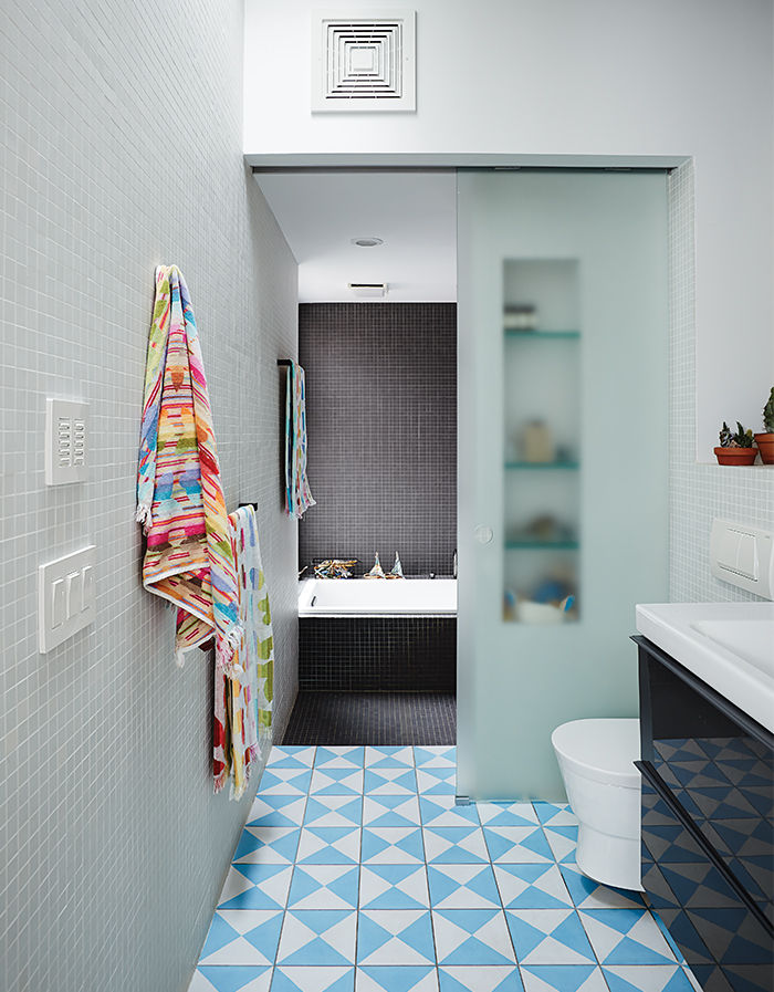 Modern Brooklyn renovation has sliding glass door in bathroom