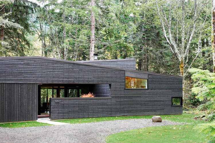 Black cedar siding on woods retreat.