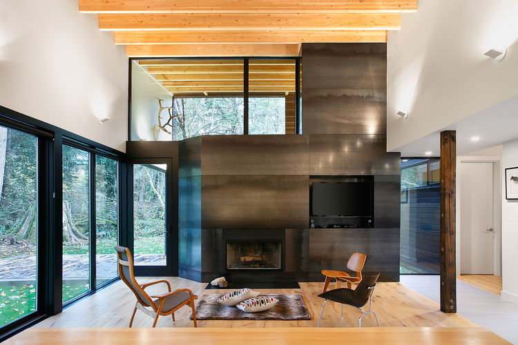 Living room with Eames Molded Plywood lounge chairs and steel-clad fireplace.