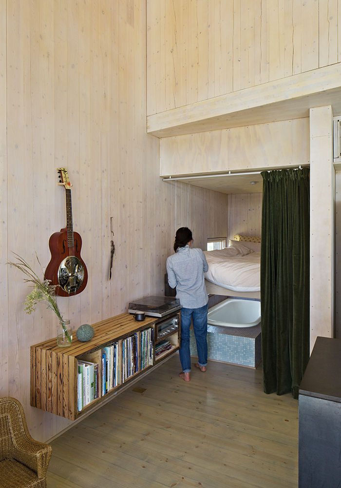 Modern prefab vacation home in Washington guest bed that lifts to reveal a bathtub