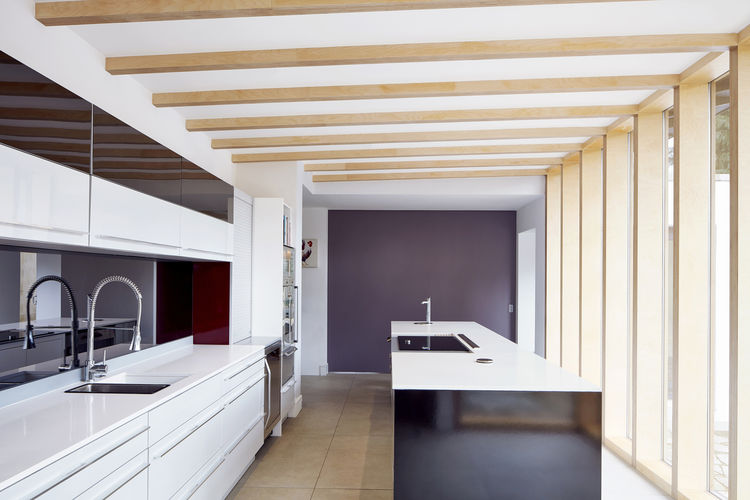 A kitchen with exposed beams and contrasting colors