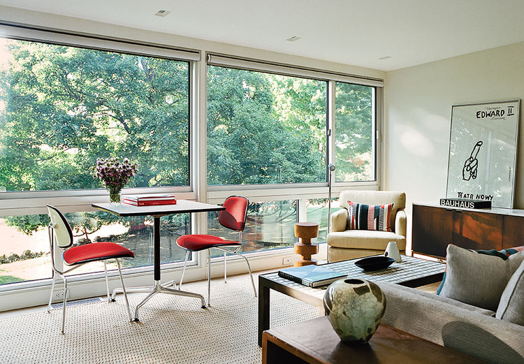 Modern guesthouse renovation in New York living room with Eames base table and plywood dining chairs by the window