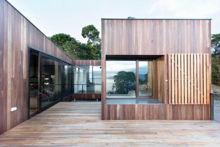 Operable timber shutters and partly-sheltered courtyard of Australian beach home by OLA Studio
