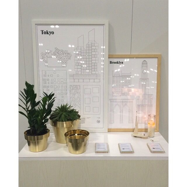 Brushed brass flower pots alongside architectural prints and candle set