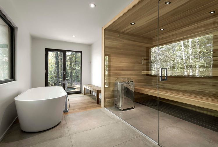 Bathroom with a wood sauna and a freestanding tub