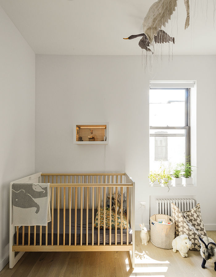 Modern Brooklyn bedroom with crib and bird mobile