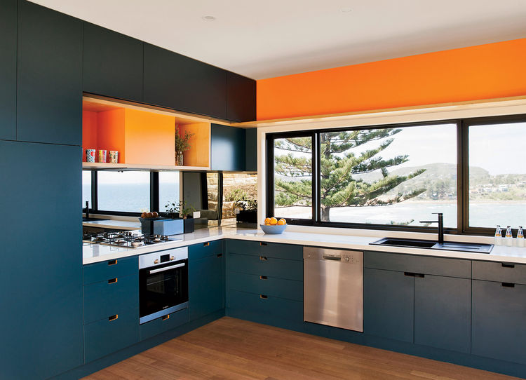 Modern beachside prefab home in Australia by Archiblox with orange and blue kitchen with bosch appliances oven cooktop hood and dishwasher