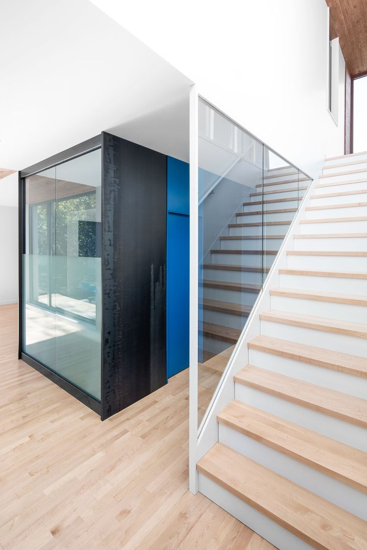 Hot rolled steel window by Enfer Design and custom maple stairs in Quebec renovation by Naturehumaine.