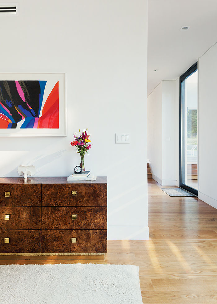 Boston prefab guest home has burl wood dresser and abstract artwork