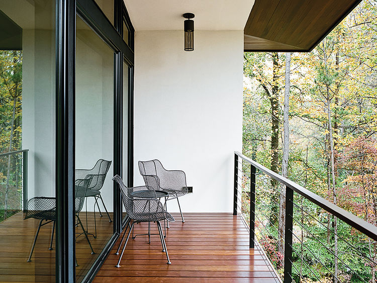 Modern home in North Carolina with wire chairs, rejuvenation pendants by hinkley lighting on the balcony