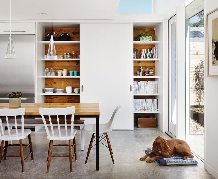 Modern Texan addition and renovation with sliding reclaimed wood pantry door in kitchen