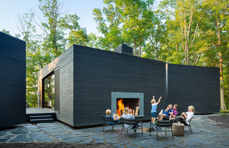 Family lounging around circle by fire in charcoal cedar riverside home.