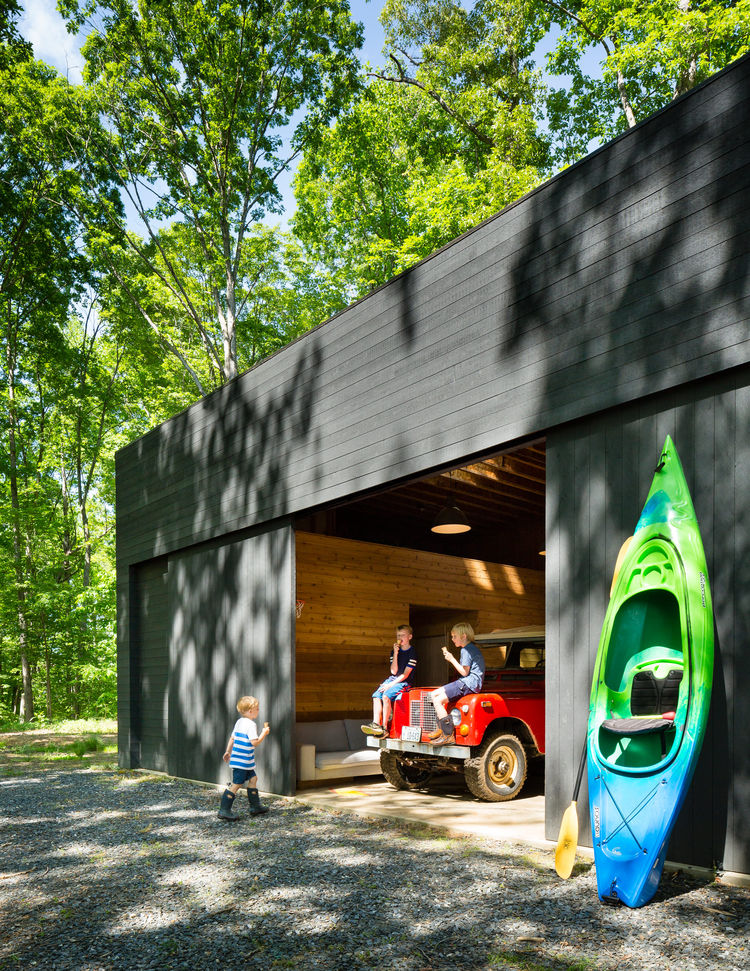 Children play inside of a charcoal cedar panel garage.