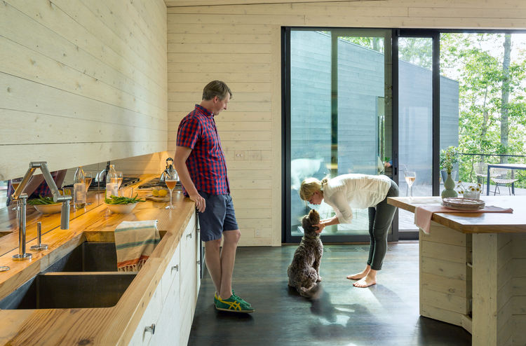 A couple and their dog relax in a wooden panel room in a Virginia riverside home.
