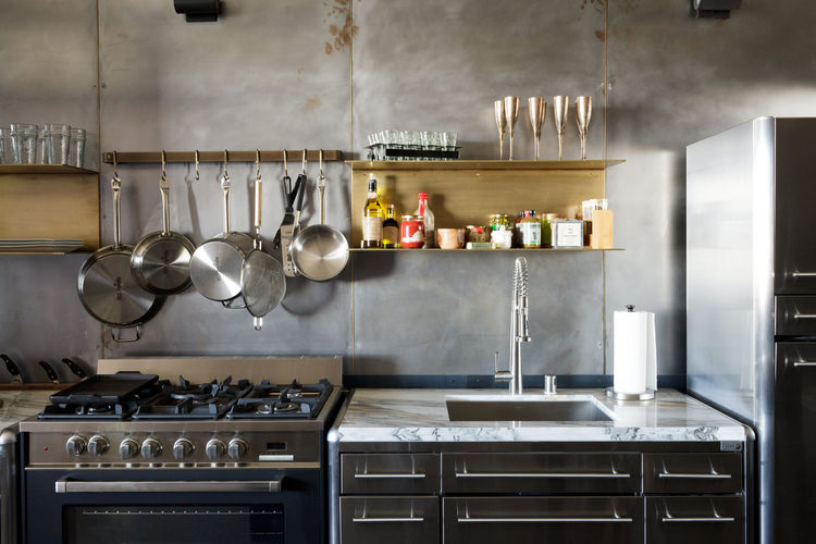 Modern Los Angeles loft kitchen renovation with brass shelves, steel wall, hayneedle pot rack, and verona range
