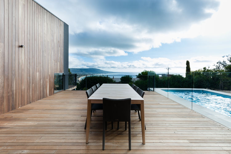 Mood Outdoor Table by Studio Segers for Tribù and silvertop ash decking on patio of Australian beach home by OLA Studio