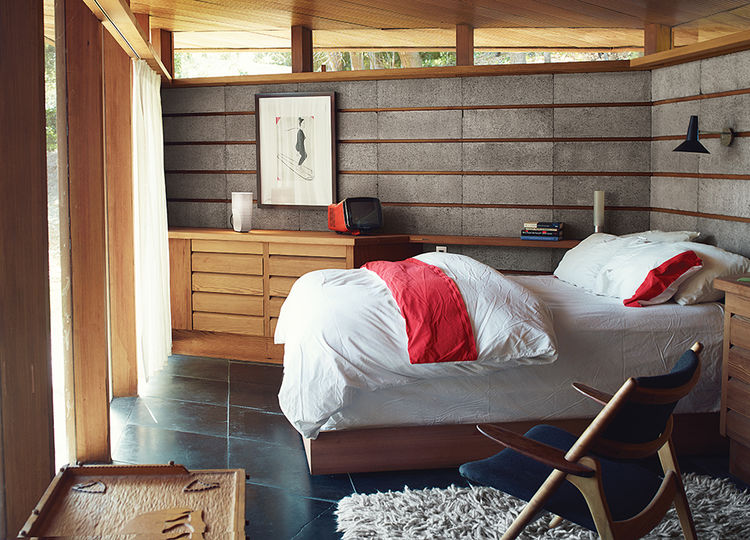 Modern home renovation in Napa includes redwood and concrete bedroom with hans wegner chair