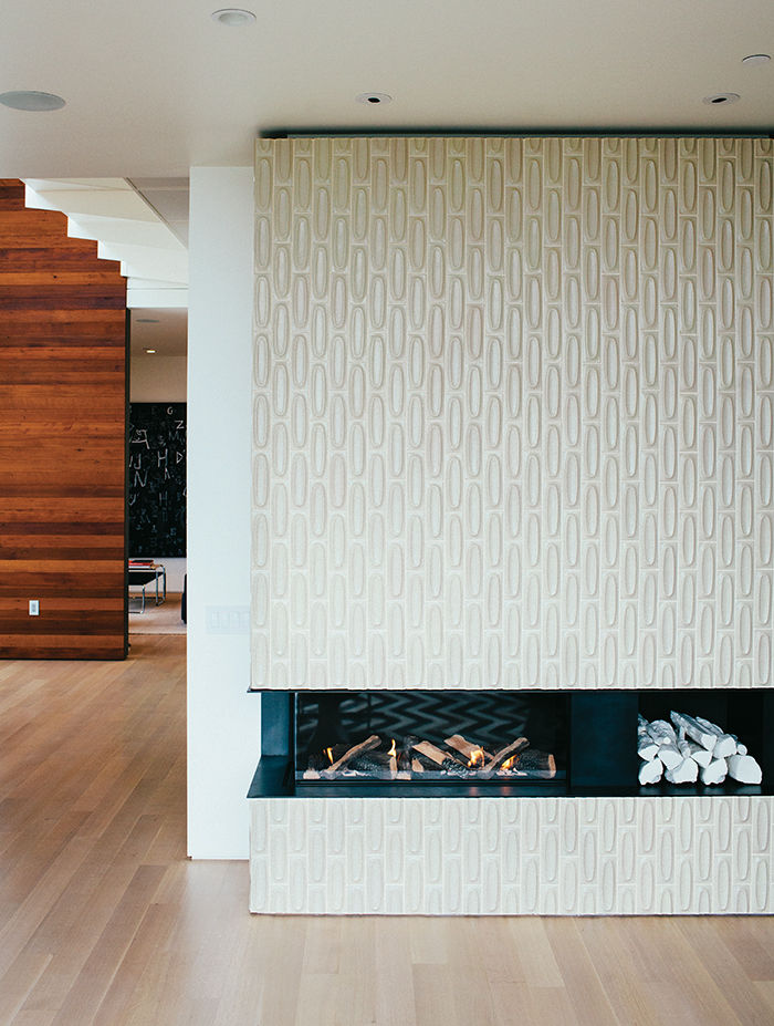 Modern renovation in San Francisco with heath ceramics tiles on the low-slung fireplace and oak floor