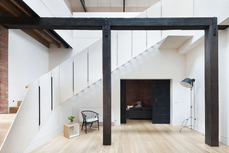 Light-filled atrium with oak floors in renovated warehouse.