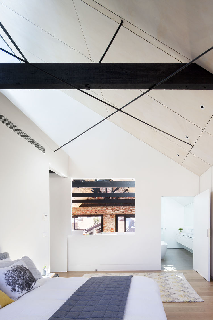 Bedroom with view into renovated warehouse's skylights.