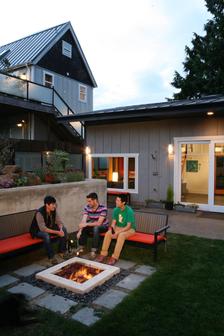 A fire pit and garden of a backyard art studio.