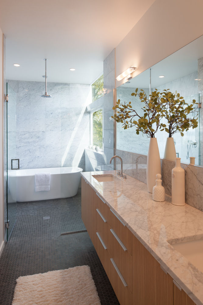 Carrara marble countertops and Wyndham Collection tub in bathroom of Seattle home by JW Architects