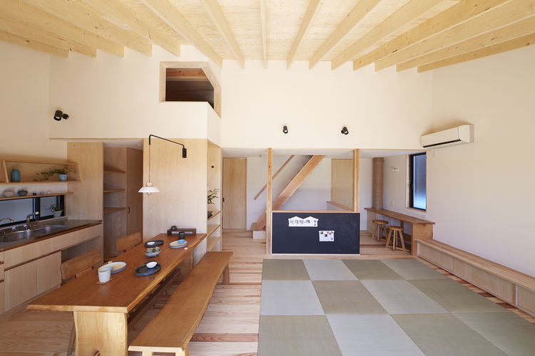 Open living and dining area in Japanese home with tatami mats.