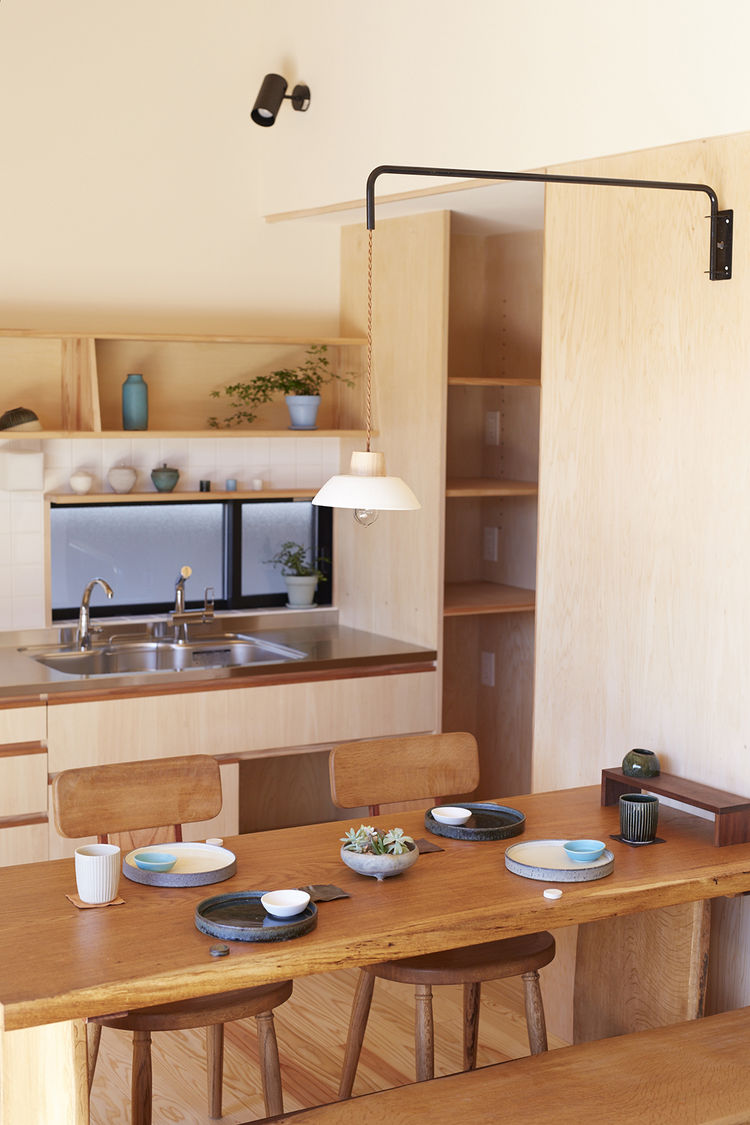 Iitaka kousaku pendant light hanging over custom dining table and chairs.