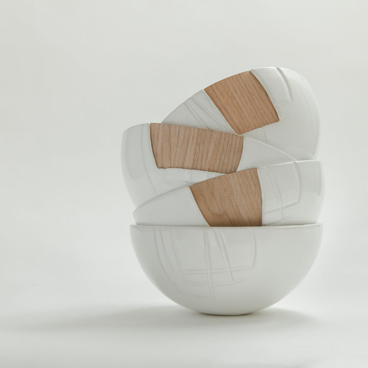 Four bowls, made up of both ceramic and wood, stacked on top of each other in a compositionally sound photograph.