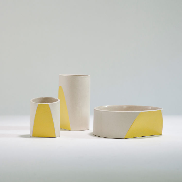 Three cream figures, each with a stripe of yellow on one of its faces.