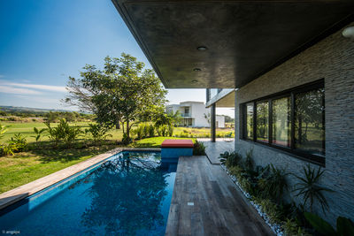 The upper level cantilevers over a wood deck and pool.