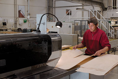 A worker runs two strips of veneer through a machine that glues the edges together.