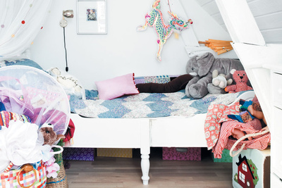 Modern kids room with white walls and bright textiles