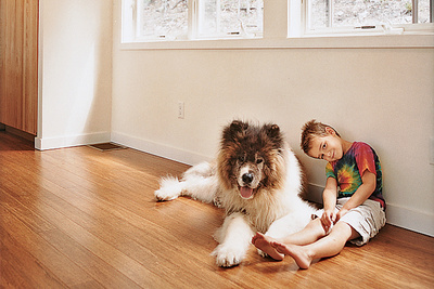 Little boy sitting on floor with pet dog