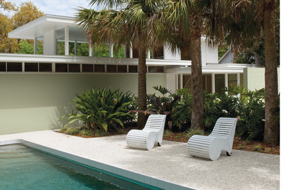 Modern outdoor pool area with curved white lounge chairs
