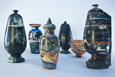 an assortment of ceramic objects in dark colorful glazes and varying shapes