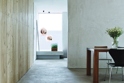 the palette of concrete floors and light wood against white walls in a living room in Germany