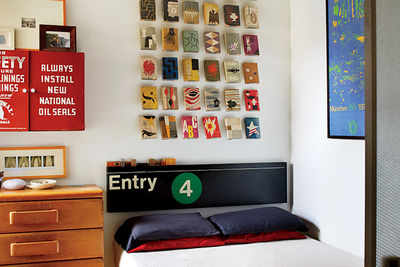 Renovated bedroom with vintage subway sign and book jackets on the wall