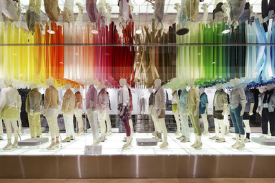 Uniqlo store with colorful paper strands hanging above mannequins