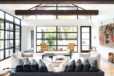 Living room with large windows, sofa, and a skylight
