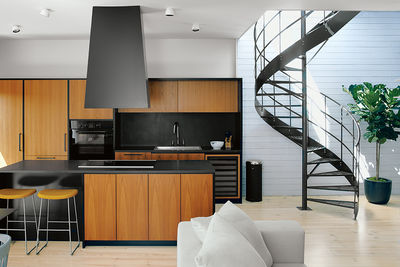 Montreal apartment kitchen with teak cabinets and spiral staircase